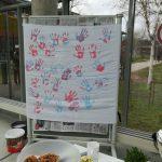 Auf dem Bild ist ein Infostand zu sehen, hinter dem ein Banner mit Handabdrücken in den Farben der Transflagge hängt.