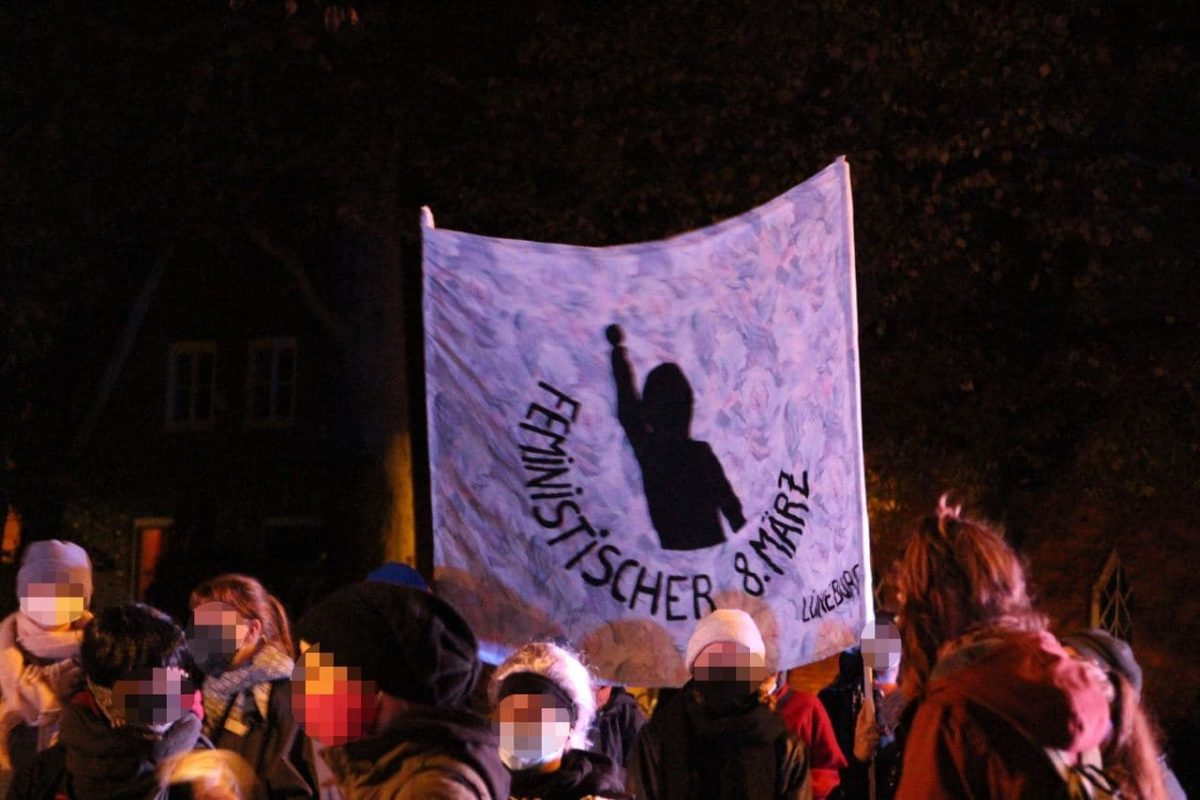 Photo from a demonstration, where in the middle of a crowd people hold a banner showing the 8th march sign: a person with raised fist.